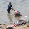 Indù che lava i panni nel Gange a Varanasi, Uttar Pradesh, India